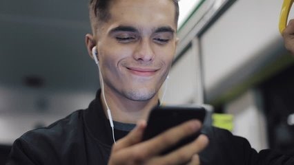 Portrait of attractive man in headphones holds the handrail, watching video on smartphone in public transport. City lights background