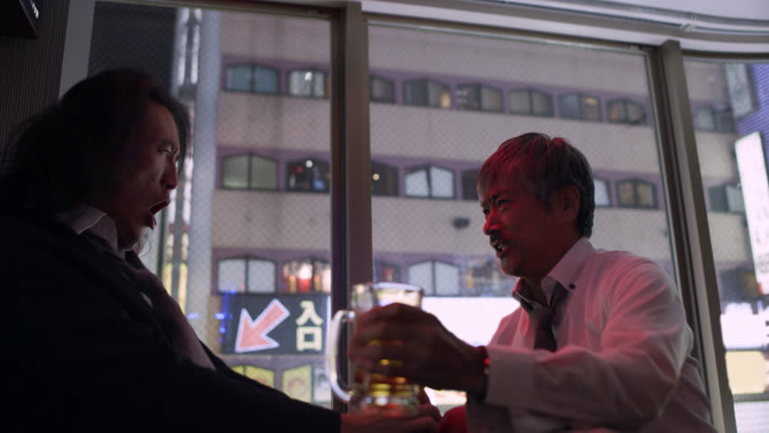 Two drunk Japanese men singing and dancing and having fun in a karaoke room with soft interior lighting.