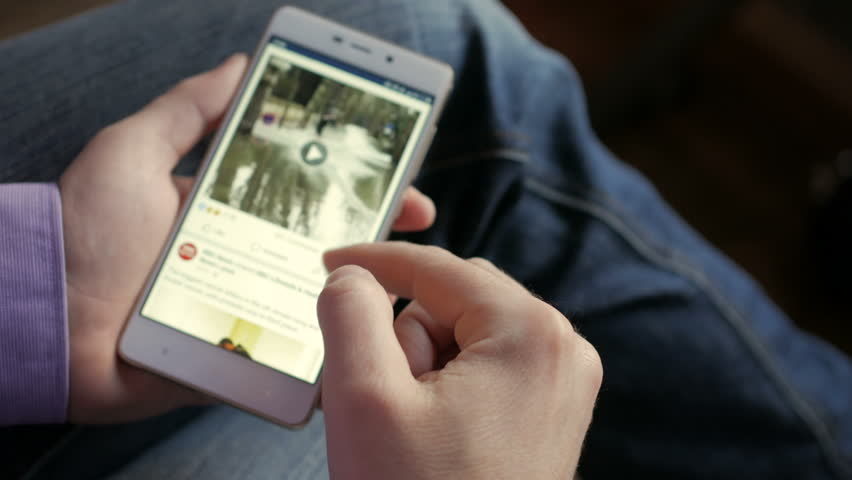 Man using his smartphone with to scroll a  Official facebook  scrolling news, tapping on screen.