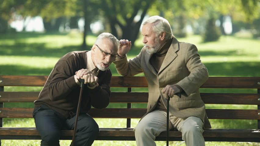 Senior gentlemen talking to his hearing impairment old friend, health problems