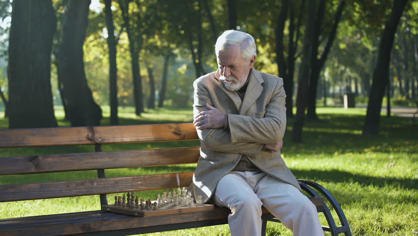 Old man sitting on bench in park alone and playing chess, retirement benefits | Shutterstock HD Video #1021901242