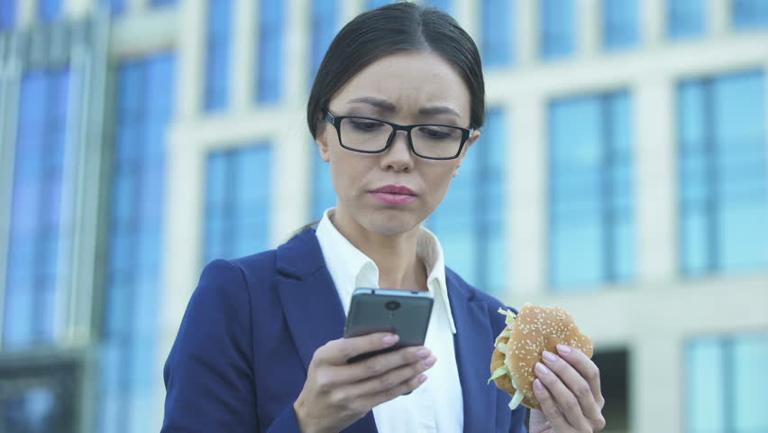 Young female manager eating unhealthy burger in hurry, checking news on phone | Shutterstock HD Video #1021904449