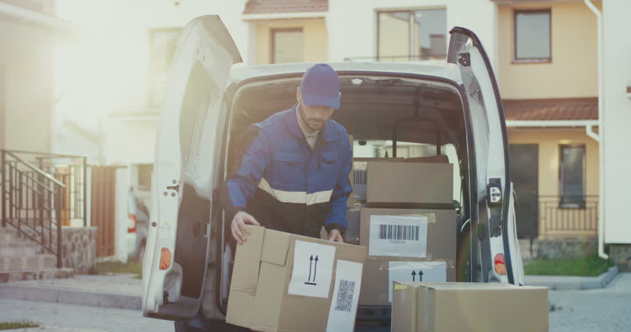 Handsome Caucasian male worker of the shipping company in the red costume and cap taking out carton parcels from the van. Outside.delivery in times of crisis , 2019-ncov , coronavirus , virus  Royalty-Free Stock Footage #1021914664