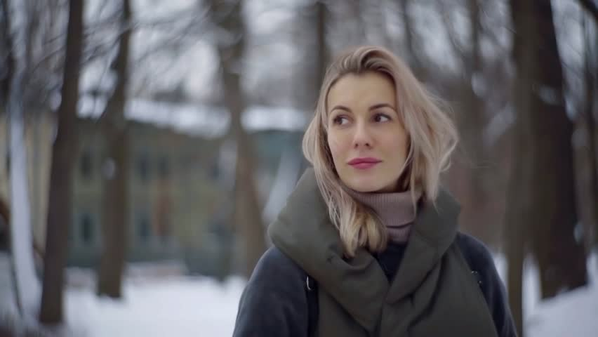 Charming pensive adult woman with blonde hair is standing alone in winter park in city, looking to side | Shutterstock HD Video #1021917340