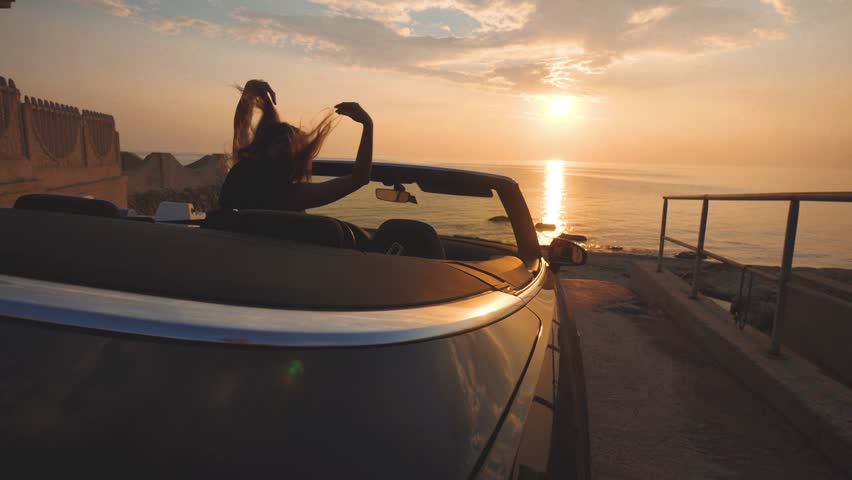 Girl dances on driver place in cabriolet car. Gentle colors of sunset over sea   Shutterstock HD Video #1021949323