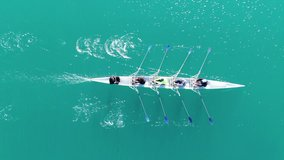 Aerial drone bird's eye view video of sport canoe operated by team of young women in emerald clear waters