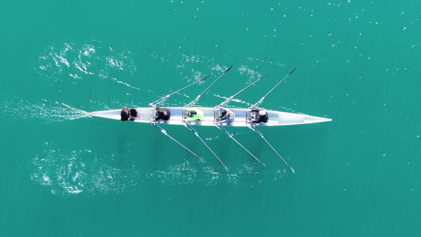 Aerial drone bird's eye view video of sport canoe operated by team of young women in emerald clear waters | Shutterstock HD Video #1021950076