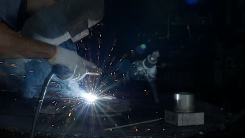 Men's hands motion with welding machine part in industrial construction factory. 4k Video Slow motion   Shutterstock HD Video #1021967371