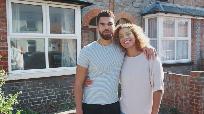 Portrait Of Young Couple Standing Outside New Home In Urban Street