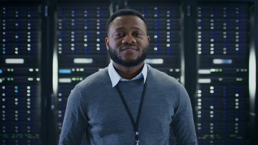 Bearded Black IT Engineer Standing and Posing with Crossed Arms in the Middle of a Working Data Center Server Room with Server Computers Working on a Rack. Royalty-Free Stock Footage #1021974661