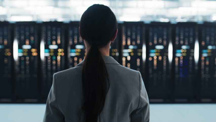 Follow Back Shot of a Female IT Chief Engineer in a Jacket Walking Towards a Server Rack in Data Center Room.