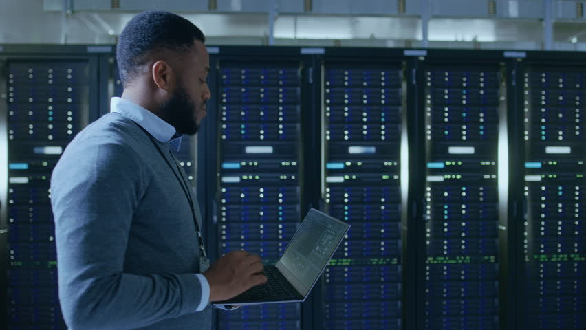 Black Data Center IT Technician Walking Through Server Rack Corridor with a Laptop Computer. He is Visually Inspecting Working Server Cabinets. Royalty-Free Stock Footage #1021974814