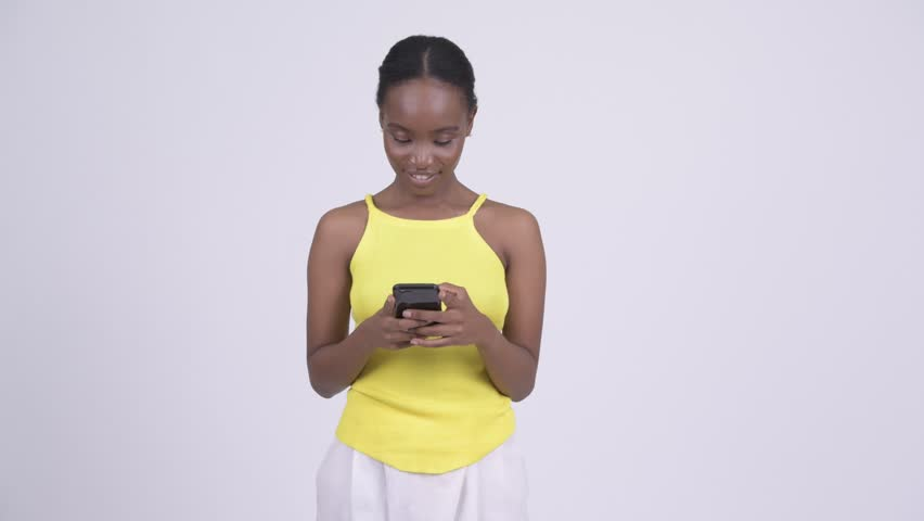 Happy young beautiful African woman using phone | Shutterstock HD Video #1021993798