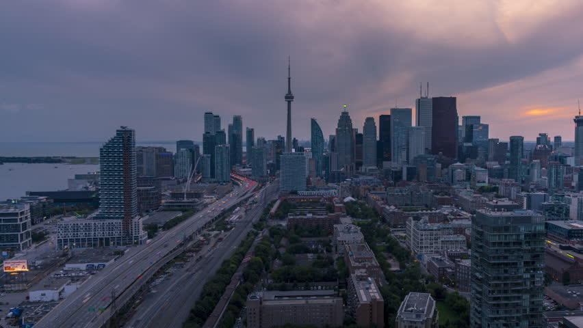 The historic and modern Toronto city skyline with car traffic travelling down the Gardiner Expressway to and from downtown Toronto during a beautiful moody sunset at night.    Shutterstock HD Video #1021994479