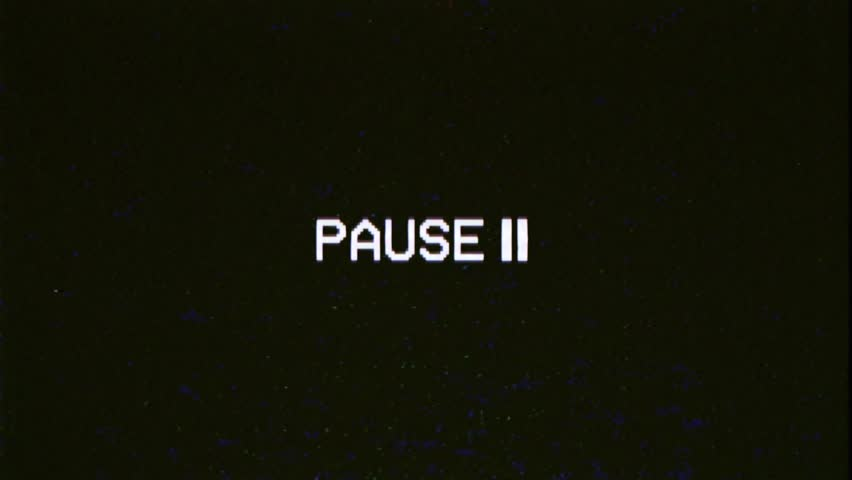 A capture of a VCR playing and pausing a VHS blank tape: the text Pause, appearing with a blinking symbol, at the center of the screen. Digital remake, regular size.  | Shutterstock HD Video #1021996057