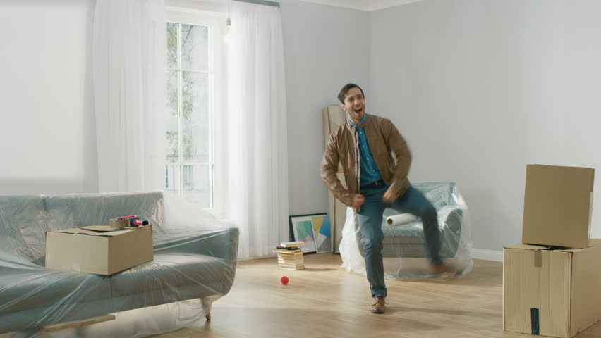 Very Happy Man Moves Into His New Apartment, Dances Excited. Guy Purchased New Home Ready to Start Unpacking Cardboard Boxes. Royalty-Free Stock Footage #1022013487