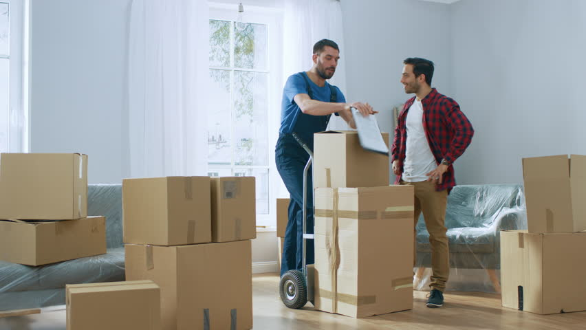 Happy New Homeowner Welcomes Professional Mover with Hand Truck full of Cardboard Boxes, Receives His Goods and Signs on Clipboard. Royalty-Free Stock Footage #1022013613