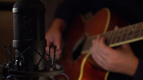 musician playing guitar on record at studio . closeup