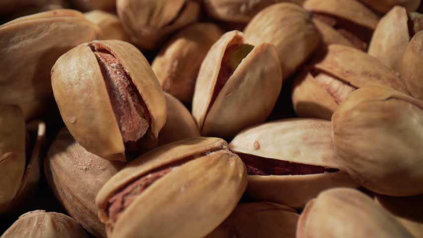 Close up of pistachios nut. The pistachio a member of the cashew family, is a small tree originating from Central Asia and the Middle East | Shutterstock HD Video #1022016826