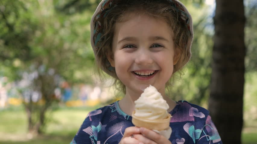 A cute little girl enjoys a delicious ice cream cone during the summer. Child with ice cream on a walk in the city park #1022025940