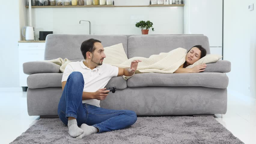 A man plays a game while his wife sleeps  #1022026138
