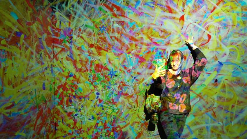 "HELSINKI, FINLAND - JAN 06, 2019: ""Massless"" Exhibition - immersive interactive graphic digital installations by Japanese artists TeamLab at Amos Rex Museum.Woman taking selfies wih new modern art"