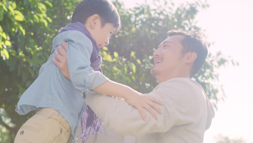 Lovely asian boy running rushing toward father in park