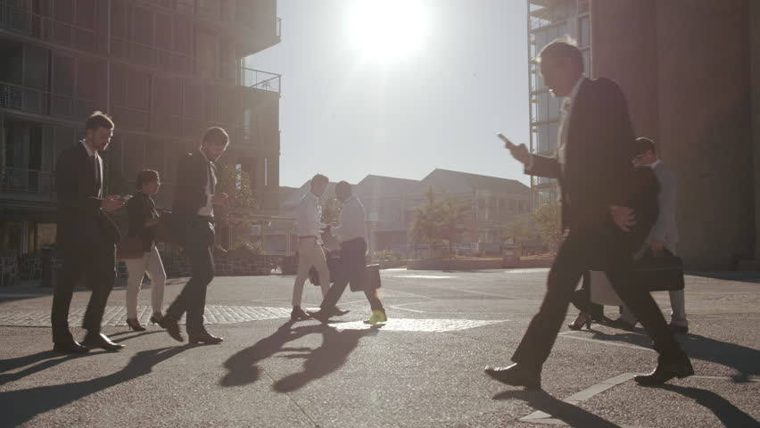 Office going pedestrians using their phones while commuting. Commuters being on their mobile phones walking to office.  | Shutterstock HD Video #1022040100