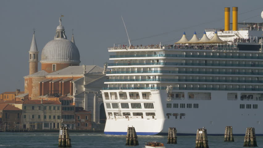 Large cruise ship sailing in Venice waterway and passing by Church of Santissimo Redentore, Italy