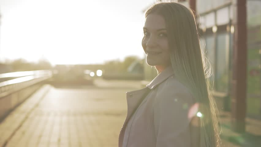Portrait of pretty caucasian woman with long hair walking in city at sunrise or sunset. Beautiful blonde woman smiling at camera and turning around in slow motion | Shutterstock HD Video #1022044837