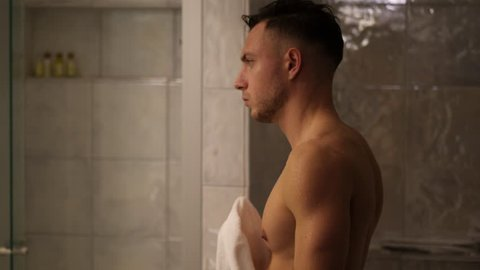 Shirtless muscular handsome young man looking at camera in bathroom in the morning, wearing only white towel around waist
