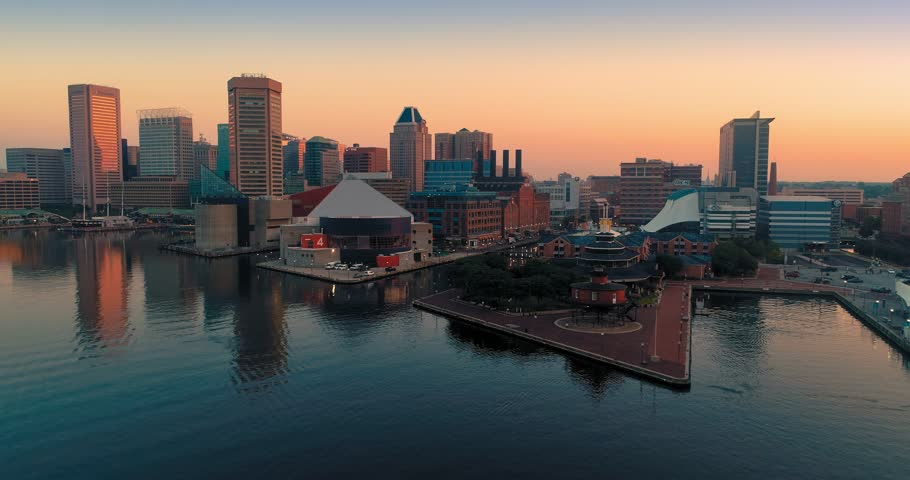 Aerial: Inner Harbor and boats and city skyline at sunrise in Baltimore, Maryland, USA.