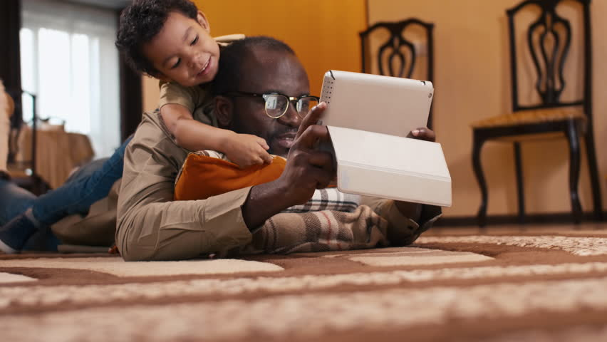 Tilt up shot of biracial boy laying on his father's back and watching over dad's shoulder on tablet computer's screen Royalty-Free Stock Footage #1022071849