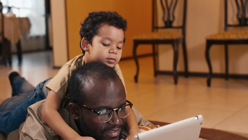 Tilt down shot of African American man laying on the floor at home with biracial son on his back and watching cartoon on tablet computer Royalty-Free Stock Footage #1022071855