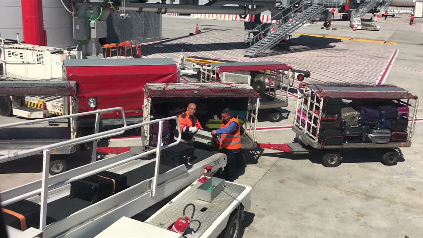 ROME, LAZIO/ITALY - APRIL 10, 2018: Unidentified baggage handlers put bags on plane at Rome airport, timelapse. It is one of the busiest airports in Europe by passenger traffic.