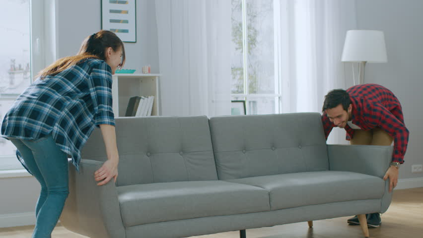 Happy Young Couple Moves New Couch into Living Room, Fall on it to Rest. Bright Modern Apartment with Stylish Furniture. Royalty-Free Stock Footage #1022087878