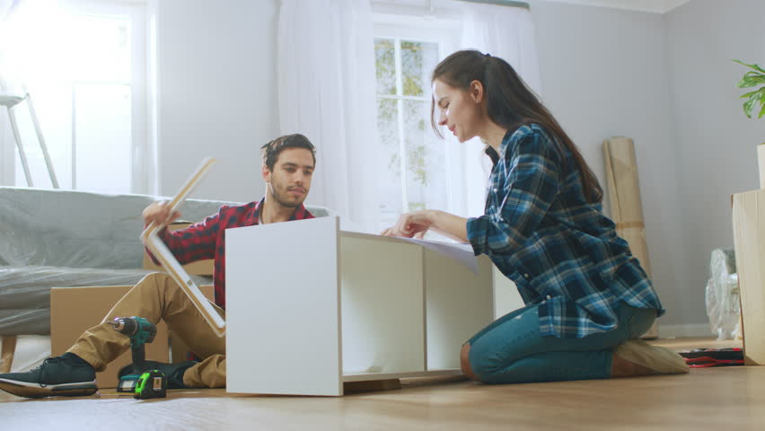 Happy Couple Assembles Furniture as a Team, Girl Reads Instructions and Boy Tightens Screw with a Drill. After Job is Done they do High Five. Moving into New Apartment, Couple Assemble Shelf. Royalty-Free Stock Footage #1022087881