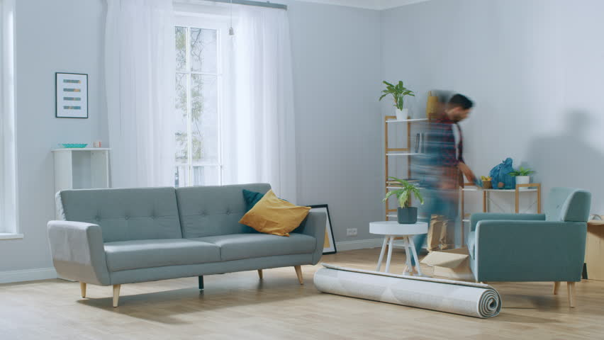 Time-Lapse: Happy Young Couple Moves into New Apartment, Arranges Furniture, Hanging Paintings, Resting after Everything is Done. Bright Modern House with Big Windows and Stylish Furniture. #1022087890