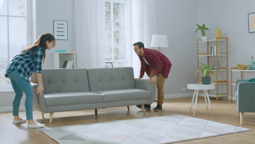 Happy Young Couple Moving New Couch into the Living Room, Fall on it to Rest. Bright Modern Apartment with Stylish Furniture. Royalty-Free Stock Footage #1022087902