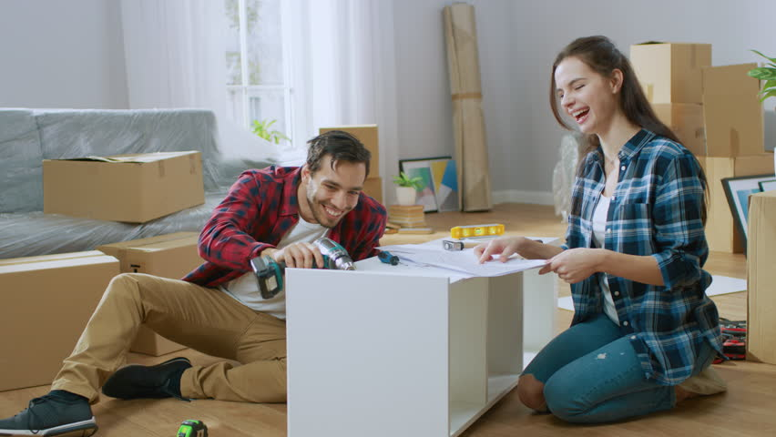 Happy Couple Assembles Furniture as a Team, Girl Reads Instructions and Boy Tightens Screw with a Drill. Moving into New Apartment, Couple Assemble Shelf. Royalty-Free Stock Footage #1022087905
