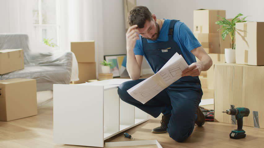 Successful Furniture Assembly Worker Uses Screwdriver to Assemble Shelf, Consults Instruction. Professional Handyman Doing Assembly Job Well, Helping People who Move into New House.   Shutterstock HD Video #1022087914