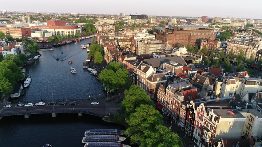 Amsterdam, Netherlands, aerial view of famous places during sunset in spring or summer.  Flying above canal and old centre district. Munttoren Bell Tower in background. Beautiful warm colors