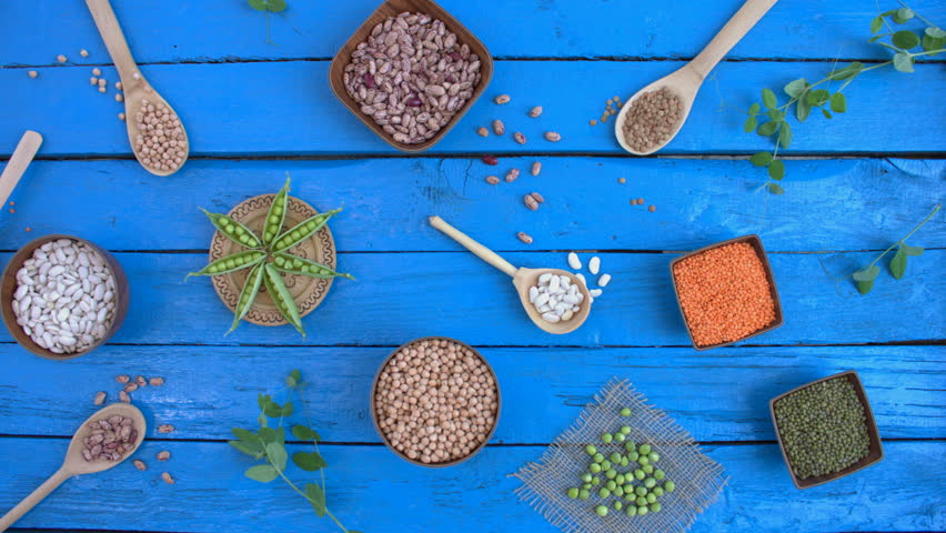 Legumes on wooden ecological background. Beans are located in unusual form on blue wooden table. Bean cultures in wooden bowls. pea lies on napkin. Camera moves from left to right.  | Shutterstock HD Video #1022092189