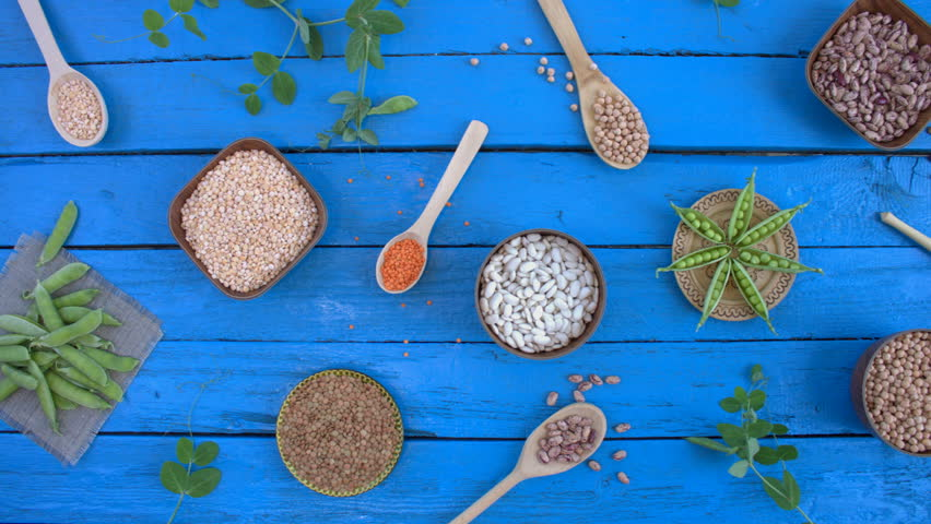 Legumes on wooden ecological background. Beans are located in unusual form on blue wooden table. Bean cultures in wooden bowls. pea lies on napkin. Camera moves from right to left.  | Shutterstock HD Video #1022093269