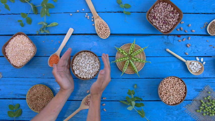 Legumes on wooden ecological background. Beans are located in unusual form on blue wooden table. Hands put bowl with white beans on table. Bean cultures in wooden bowls. pea lies on napkin.   Shutterstock HD Video #1022098726