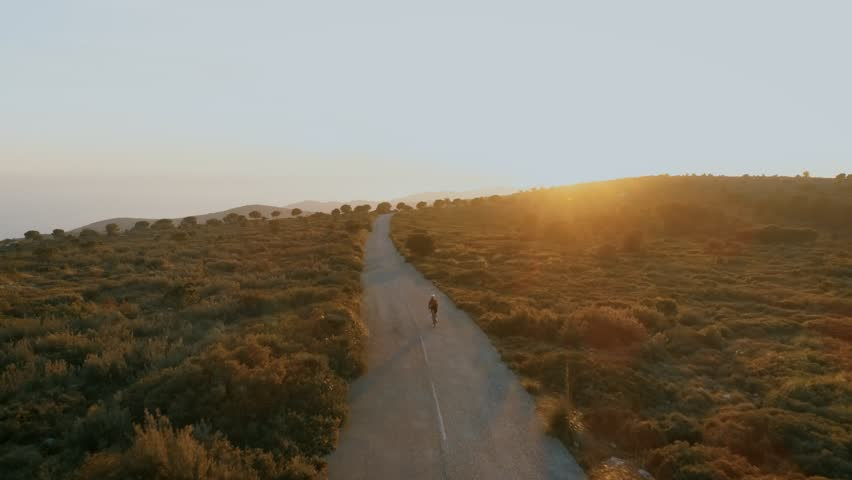Sunset flare sun beam light in lens of aerial drone footage of young female woman on road bicycle ride up winding mountain pass. Epic and motivational landscape or concept for training or sports | Shutterstock HD Video #1022101726