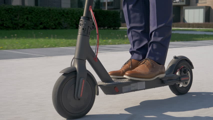 Close up - Adult male in business attire riding with electric scooter to work   Shutterstock HD Video #1022107555