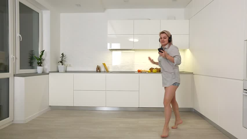 Happy young woman dancing in kitchen in the morning listening to music on smartphone #1022110897