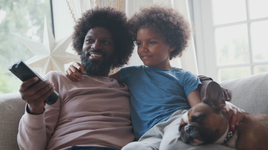 Smiling middle aged black father and pre teen son reclining on sofa together watching TV with their pet dog, dad holding remote control, low angle, close up