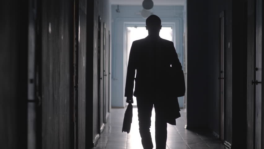 Tilt down shot of silhouette of businessman wearing formal suit and carrying coat and briefcase leaving office and walking towards the camera along hallway
